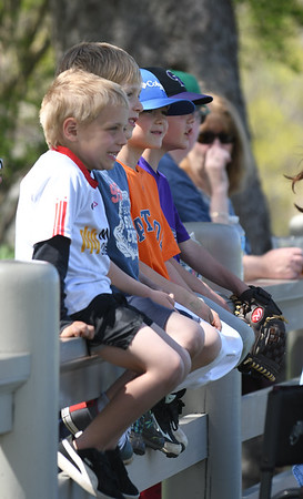 JIM VAIKNORAS/Staff photo A group of kids sit on a fence in the shade  to watch Lynn Live Oaks play baseball against  the Portsmouth Rockinghams at the Spencer-Peirce-Little farm in Newbury Saturday.