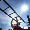 BRYAN EATON/Staff photo. Ginny Bishop, 9, moves along the monkey bars under the shining sun as the Boys and Girls Club moved activites outdoors. The weather is forecast to be warm and sunny today, though showers are likely later in the day with possible lighting and thunder.