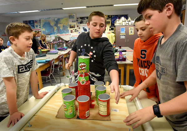 "BRYAN EATON/Staff photo. Amesbury Middle School sixth-graders are making seismometers in Gale Regis' class this week and next week will be testing those from the different teams to see who has the best design.  Making adjustments to their ""Port-a-Pringle"" are, from left, Kyle Palen, 12, Matthew Anderson, 11, Owen Brannelly and Brody Tonks, both 12."
