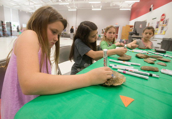 JIM VAIKNORAS/Staff photo Genevieve D'Angelo,8, Sophia Vasapolli, 8, Abby Daniel,8, and Julianna Moore,9, paint turtle markings on rocks during a program about Blandings Turtles at the Bagnall School in Groveland. Older girls working on their Bronze Award were working with younger girls teaching them about turtles through crafts.