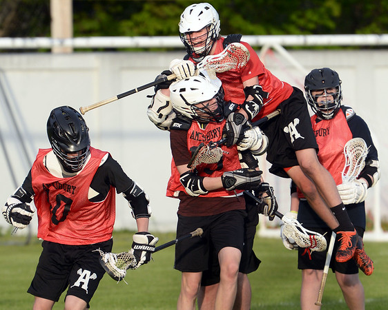 CARL RUSSO/Staff photo. Amesbury's Zachariah Daniels jumps on top of Leif Riley to celebrate with the other Indians Riley's goal. His goal was the first one of the game. This year Amesbury High School sponsored boys lacrosse for the first time, and the program competed at the JV level for its inaugural season. Monday night the program celebrated its first ever senior night, honoring it only senior, Carter Castay and his family. 5/14/2018