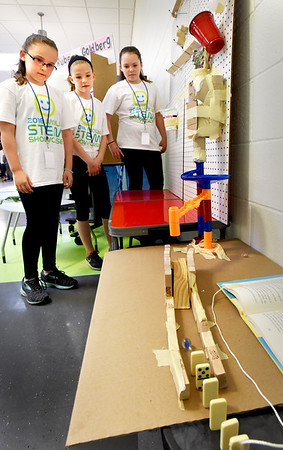 BRYAN EATON/Staff photo. Team members, from left, Grace Daigle, 11, Devon Davis, 11, and Ani Mellett, 10, watch as a marble dropped is just ready to knock down Dominoes. They created a Rube Goldberg contraption, which takes a long, complicated way to do a basic function, in this case simply rolling the marble to knock down the Dominoes.