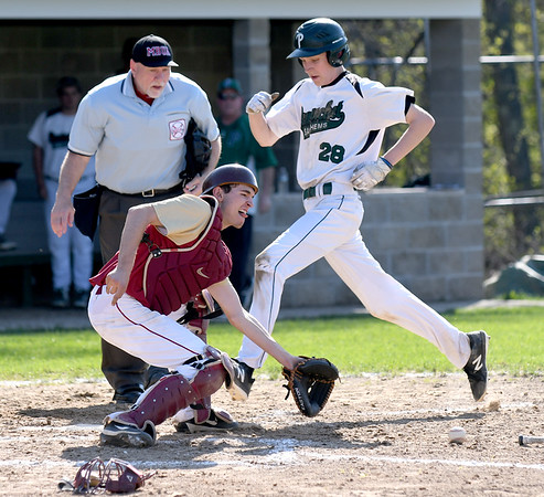JIM VAIKNORAS/Staff photo Pentucket's Nick Cochran scores on a tag play as Newburyport's Kenny Hodge waits for the throw at Pentucket Tuesday afternoon.