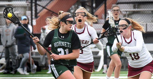 BRYAN EATON/Staff photo. Manchester-Essex player Drew Charlton gets the pressure from Newburyport's Molly Rose Kearney and Madison Johnston.