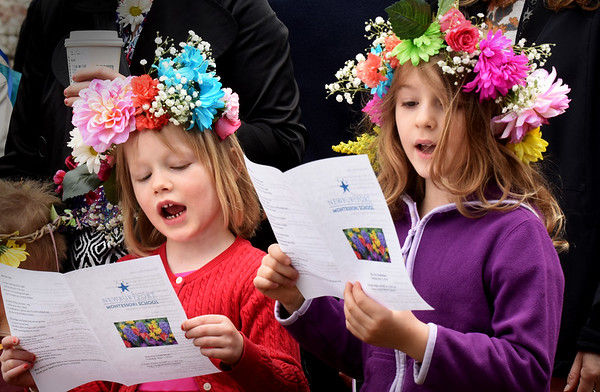 """BRYAN EATON/Staff photo. Josie Wizda, left, and Saskia Howe, both 6, sing """"This Land is Your Land"""" at Brown Square in Newburyport on Tuesday morning. The Woody Guthrie song was one of several the Newburyport Montessori School students sang, this year with elderly residents of Avita attending as guests."""