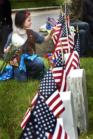 BRYAN EATON/Staff photo. Audrey Paciulan, 9, of Girl Scout Troop 89109 along fellow scouts and cub scouts placed daisies on the graves at the Veteran's Cemetery on Pond Street in Newburyport.