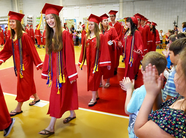 """BRYAN EATON/Staff photo. Amesbury High School graduates parade past applauding kindergartners in the Cashman School gymnasium as they do a """"walk through"""" ahead of their graduation Friday night. Many of the seniors attended the school with some of their teachers still there after the past eight years since they left."""