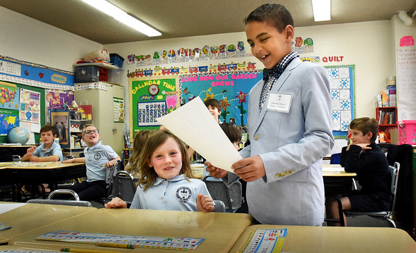 BRYAN EATON/Staff photo. Immaculate Conception School second-grader Anthony Davis, 8, looks over first-grader Ella Reddie's mathwork as he visited different classrooms on Tuesday morning. The was Principal For a Day, his family winning one of the raffles at the Newburyport school's annual eight-week fundraiser.