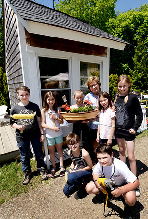 BRYAN EATON/Staff photo. Sparhawk School students have converted this run-down outbuilding into a literary cottage. Front, from left, Sonja Aspeslagh, 11, and Zuri Silver, 10. Back, from left, Eli Paullis, 11, Pilot Davenport, 9, Willow Dixon, 9, teacher Paula Render, Lyla Hall, 7, and Sorelle Hamilton, 11.