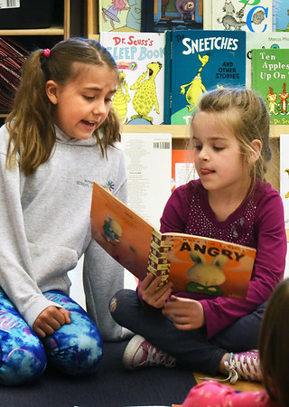 """BRYAN EATON/Staff photo. Third-grader Elise Kennedy, 9, left, reads """"When I'm Feeling Angry"""" to kindergartner Isabelle Vigeant, 6, a book about a rabbit who is angry and learns to deal with it. They were in Reading Buddies, where Laurie Barrows' third grade and Linda Gershuny's kindergarten classes get together once a week with the older students getting a sense of helping younger ones and the kindergartners get to feel comfortable with older students and get excited about reading."""
