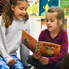 "BRYAN EATON/Staff photo. Third-grader Elise Kennedy, 9, left, reads ""When I'm Feeling Angry"" to kindergartner Isabelle Vigeant, 6, a book about a rabbit who is angry and learns to deal with it. They were in Reading Buddies, where Laurie Barrows' third grade and Linda Gershuny's kindergarten classes get together once a week with the older students getting a sense of helping younger ones and the kindergartners get to feel comfortable with older students and get excited about reading."