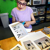 BRYAN EATON/Staff photo. Catherine Melnick, 12, cuts out elements of her science project display for the Nock Middle School's Science Fair next Monday at the Newburyport Rec Center. The projects relate to consumer project investigation and she decided to researsh dry erase markers to test which ones work best on different surfaces and other criterior.