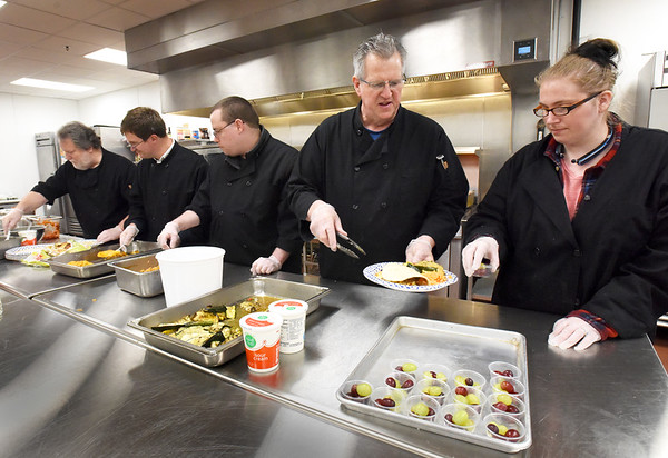 BRYAN EATON/Staff Photo. Shared Living Collaborative, a nonprofit working with special needs individuals, will be hosting the Rotary Club's Kentucky Derby party this weekend and preparing the food. Making lunch earlier this week are, from left, Mark Lynch, kitchen manager; Michael Kennefick; Jason Lehy; Chris Coogan, kitchen manager and Heather Nusbaum.