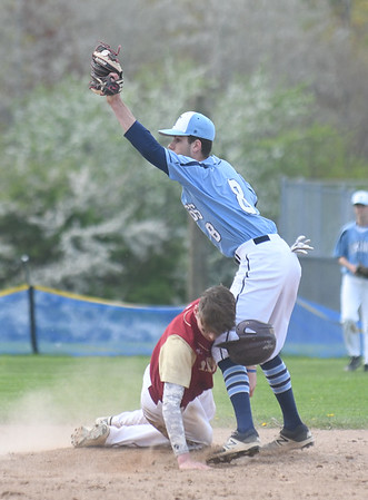 JIM VAIKNORAS/Staff photo Triton's Cameron Gilroy raises the ball after tagging Newburyport's Jacob Buontempo at Triton Thursday.