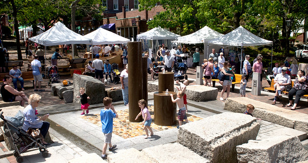 JIM VAIKNORAS/Staff photo Kids play in the Inn Street fountain surrounded by venders at the Newburyport Spring Fest Monday afternoon.