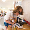 JIM VAIKNORAS/Staff photo Lucas Shorten, 10 looks through a microscoper at the STEM Expo at the Molin School in Newburyport Friday His project was to compare the different forms of microscopic life in each type of water, pond, ocean , standing, and tap.