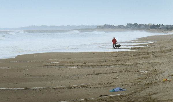 BRYAN EATON/Staff Photo. A dog walker walks among the splash over from high waves at Salisbury on Tuesday afternoon. The warm weather also brought some people to the take-out stands at the beach center.