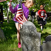 BRYAN EATON/Staff Photo. Caroline Berg, 9, replaces the U.S. flag on the grave of Joseph Wadleigh, who died in 1799 and fought in the American Revolution, at the Corner Cemetery in Amesbury on Tuesday morning. She and other third-graders from Amesbury Elementary School also replaced the flags of veterans at Prospect Hill Cemetery.