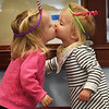 BRYAN EATON/Staff Photo. Friends Quinn Dulany, left, and Tea Zoric, both one and a half, and from Newburyport, give a kiss wearing their princess crowns made out of pipe cleaners. They were in the activities room of the Children's Room at the Newburyport Public Library where their mothers made the crowns with provided supplies.