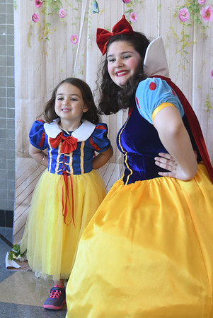 JIM VAIKNORAS/Staff photo Ella Comora, 3, poses with freshman Sofia Saraiva at the Princess Tea Party fundraiser for the Freshman Class at Amesbury High School Saturday. The event featured Pin the Kiss on the Frog, Princess Bowling, dancing, cup cakes, Princess Limbo, and finger sandwiches.