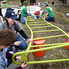 BRYAN EATON/Staff Photo. Timberland employees prepare a monkey bar for attachment to the rest of the playground equipment.