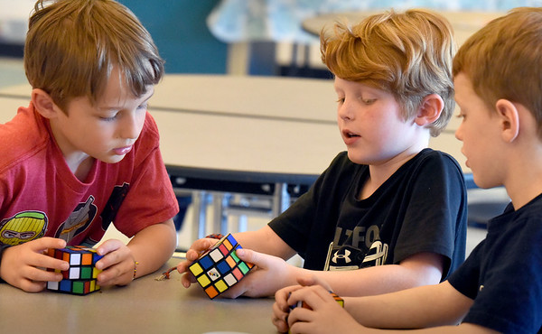 BRYAN EATON/Staff Photo. Dylan Malio, center, gives tips on solving the Rubik's Cube to Bennett, Waddell, left, and Lucas Gandolfi, all 7, at the Newburyport YWCA's afterschool program at the Bresnahan School. He's been interested in the cube for two years and the staff says he's pretty good at it.