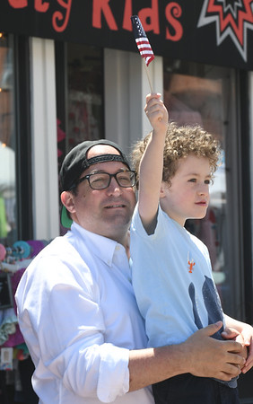 JIM VAIKNORAS/Staff photo  Anthony Dziepak holds his son Owen Dziepak 6, as he waves the flag to the passing Memorial Day Parade on State Street in Newburyport  Monday morning.