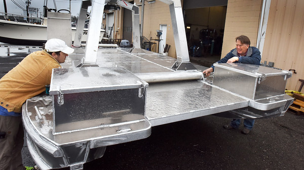 BRYAN EATON/Staff Photo. Dominic Manganelli, left, assists Goudey as they finish preparations for the seawood harvesting boat to be shipped to Puerto Rico.