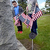 BRYAN EATON/Staff Photo. Jackson Dixey, left, and Colby Nash, both 9, did their part with fellow Amesbury Elementary School third-graders in replacing old U.S. flags with new ones on the graves of veterans. Close to 400 flags were put in place in the Corner Cemetery and Prospect Hill Cemetery in Amesbury on Tuesday morning.