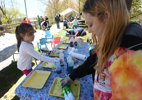 JIM VAIKNORAS/Staff photo Bentlee Dragon, 6, makes a tie dye shirt with some help from Noel Allen, 15,  at the annual Salisbury Art Walk on the Rail Trail Saturday.