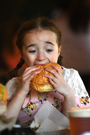 JIM VAIKNORAS/Staff photo Jilll Delude, 8, of Newburyport enjoys a large burger at the Riverwalk Brewing Co.Saturday during a fund raiser to build an inclusive playgound at the Bartlet Mall.