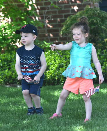 JIM VAIKNORAS/Staff photo  Griffin Rice , 3, and Lydia D'Andria, 3, watch as the Amesbury Memorial Day Parade makes it's way up Main Street  Monday.