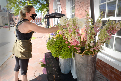 BRYAN EATON/Staff photo. With the wedding part of her flower business heavily affected by the coronavirus, Amy McLaughlin, is selling flowers from the sidewalk on her Middle Street shop in Newburyport.