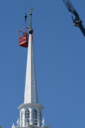 BRYAN EATON/Staff photo. People walking around downtown Newburyport on Wednesday morning and looking up saw some activity atop the Unitarian Church as a man was suspended from a crane. Ericsson, a telecommunications company, was doing some testing on the cell tower inside the steeple.