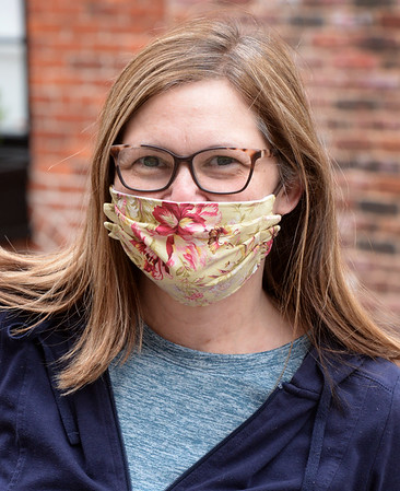 BRYAN EATON/Staff photo. Brenda Cronin of Newburyport wears a mask of flowers walking on Newburyport's Inn Street that she bough online.