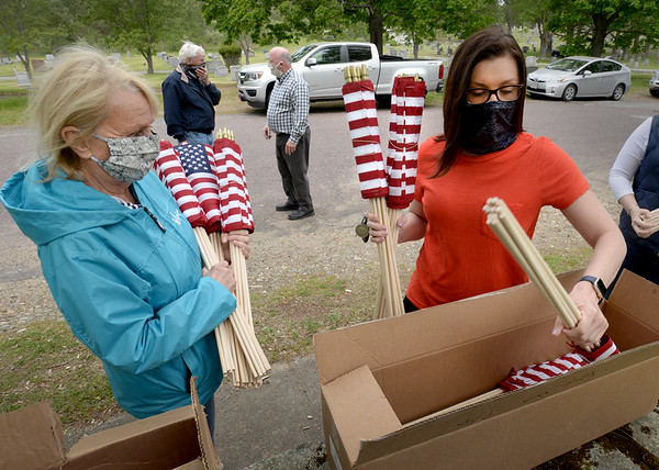 BRYAN EATON/Staff photo. Volunteers Karen Cameron, left of Newbury, and Amesbury Mayor Kassandra Gove remove American flags from boxes on Saturday morning. They were two of over a dozen volunteers replacing worn flags at the graves of soldiers at St. Joseph's and Union Cemeteries in Amesbury.
