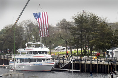 BRYAN EATON/Staff photo. Jesse Lombard of Newburyport hung a huge American flag above the new park space on Newburyport's waterfront for a Memorial Day observance from 9:00 a.m. until 1:00 p.m. on Monday. Last year he hung it over the Bartlet Mall for the Memorial Day Parade which passed by.