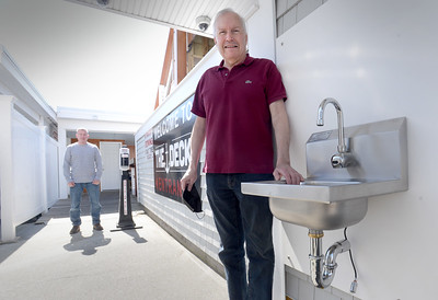 BRYAN EATON/Staff photo. Mark Audette, owner of The Deck in Salisbury, has installed hand washing sinks around the restuarant that will have soap dispensers and electric driers. He also has retained Patrick Reddy, back, of Red's Restrooms to maintain hand sanitizing stations.