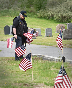 BRYAN EATON/Staff photo. John Clifford was one of the volunteers replacing worn American flags at soldiers' graves at St. Joseph and Union Cemeteries in Amesbury on Saturday morning. The Newburyport resident served in the U.S. Air Force.