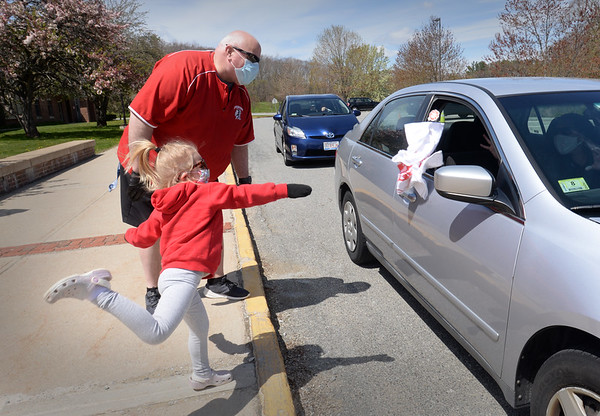 """BRYAN EATON/Staff photo. Amesbury High School administrators held a """"dance party drive through"""" for teacher appreciation on Friday afternoon giving away t-shirts with Amesbury High logo and red masks, the Amesbury High colors, made by community members Jennifer Munro Logan, Mary Ellen Shirshac, Kari Caulfield Bateman, Sarrah Young, and Kerry McDonald Richard. Principal Elizabeth McAndrews, vice-principal Glen Gearin and vice-principal Danielle Ricci along with her husband Ryan Ricci,  who was the DJ, and daughters Abby, Gracie and  newborn Emmy were handing out the gifts. Here Abby helps out throwing a t-shirt into a teacher's car as Gearin watches."""