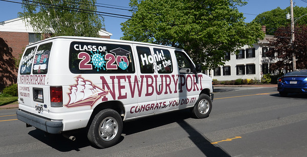 BRYAN EATON/Staff photo. One of a half dozen specially decorated vans leave Newburyport High School to drive past the houses of graduates to celebrate their accomplishments during the diminished school year. School officials including Mayor Donna Holaday made the ride, horns honking as they drove down the streets of Newburyport on Friday afternoon.