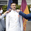 BRYAN EATON/Staff photo. MIchael Denner's parents, MIchell Denner Duratti, left, and father Russ Denner attache his ensign's insignia after his swearing in in the U.S. Navy.