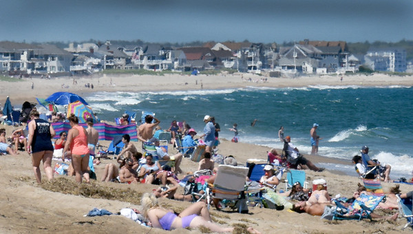 BRYAN EATON/Staff photo. Salisbury Beach certainly had its share of sun whorshippers on Wednesday afternoon as the temperature was 92 degrees., here, near access point #12, with Seabrook Beach in the distance as New Hampshire beaches are still officially closed. Photographers note: The compression of a long telephoto lens gives the impression people are closer together than actually are.
