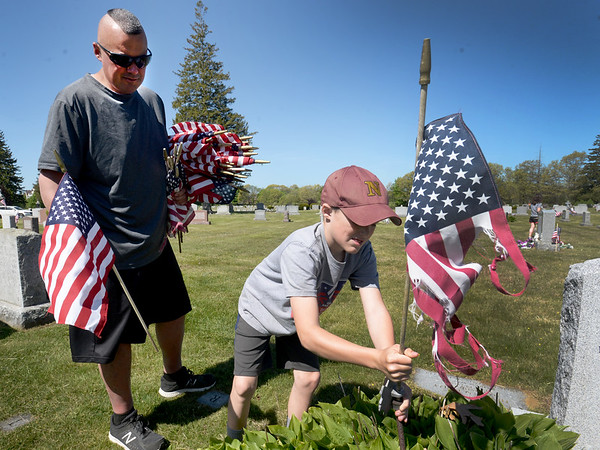 BRYAN EATON/Staff photo. Jack Webber, 9, removes a tattered American flag from a grave at St. Mary's Cemetery in Newburyport as his father, John, waits with a replacement. Webber, who's a teacher at the Nock Middle School, always arranged for students to help the Veteren's Office place the flags at St. Mary's and the Belleville Cemetery in years past, but with schools out and concern about the coronavirus, that wasn't possible this year, so a handful of adult volunteers stepped in.