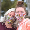 BRYAN EATON/Staff photo. Julia Cross, left, and her daughter Liv of Groveland colorful floral masks on Newburyport's Waterfront Park their friend Lisa O'Connor made.