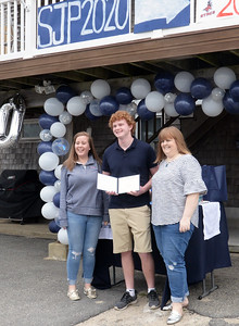 BRYAN EATON/Staff photo. Flanked by his sister Sheelagh, left, and mom, Sarah, Sean Bellamy shows off his diploma to family and neighbors at his Salisbury Beach home.