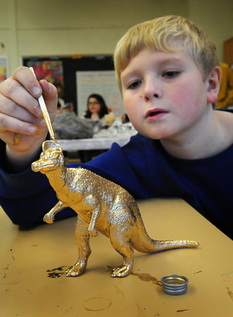 Salisbury: Noah Saboliauskas, 9, of Newburyport paints his dinosaur gold in the art room at the Boys and Girls Club in Salisbury. The corythosaurus was one of several of the reptiles that children could choose from and build from a kit. Bryan Eaton/Staff Photo