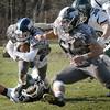 BRYAN EATON/Staff Photo. Triton back Bryan Hughes is grabbed by Pentucket linebacker Noah Malhi.