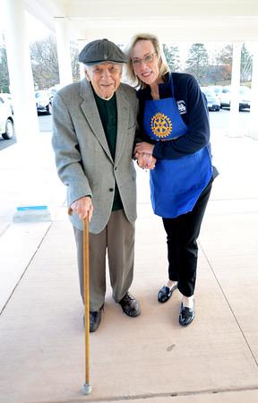 JIM VAIKNORAS/Staff photo Alex Terzis walks with Ann Ormond at the Lions Club's Thanksgiving dinner at the Newburyport Senior Center.