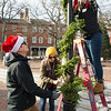 JIM VAIKNORAS/Staff photo Todd Derby , Vanessa Ayersman and Liz Gross decorate a lamp post in Market Square in Newburyport Saturday morning. The trio were a few of about 30 who volunteered with the Chamber of Commerce to bring Holiday cheer to the city.